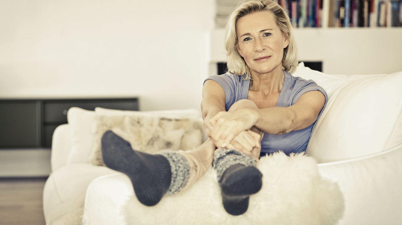 Hormone in den Wechseljahren: Lächelnde ältere Frau mit sitzt entspannt auf dem Sofa.