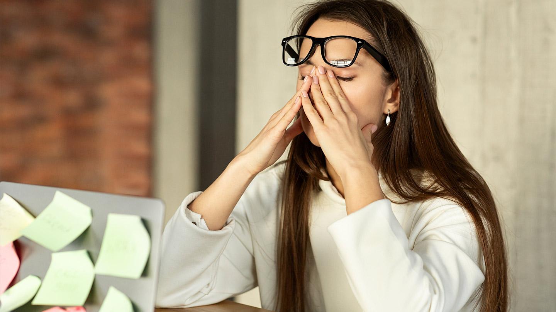 Trockene Augen: Junge Frau hat sich die Brille auf die Stirn geschoben und hält die Hände vor die Augen.