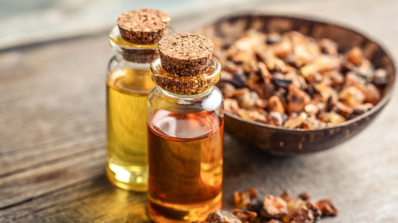 Myrrhe: Zwei Glasfläschchen mit gelber und goldbrauner Flüssigkeit und ein braunes Schälchen mit Harzstückchen stehen auf Holzgrund.